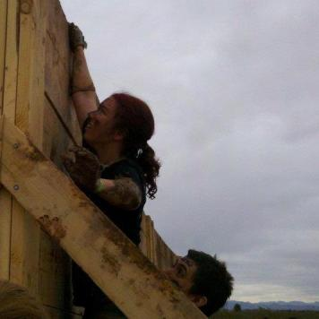 "alt=""Jessica scaling a 10 foot wall as a friend lifts her up"""