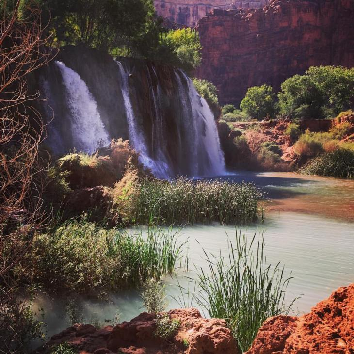 alt=Old Navajo Falls at the Havasupai Reservation. Waterfall set in the canyon with a blue pool at the base.